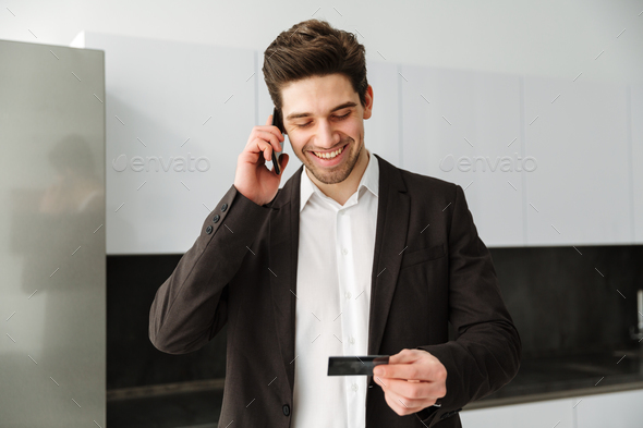 Happy young businessman talking by mobile phone holding credit card. - Stock Photo - Images