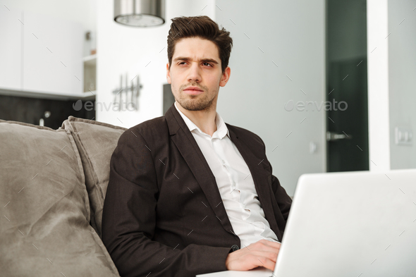 Concentrated young businessman in home - Stock Photo - Images