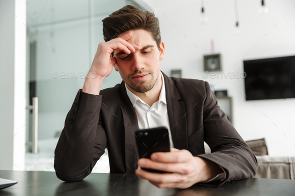 Serious young businessman using mobile phone. - Stock Photo - Images