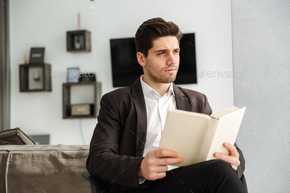 Serious young businessman sitting in home - Stock Photo - Images