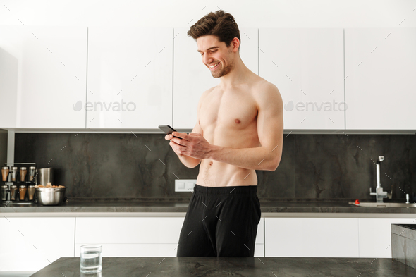 Happy cheerful naked man standing in kitchen - Stock Photo - Images
