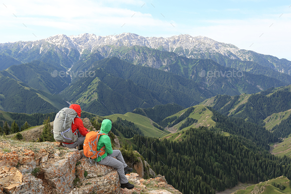 Two successful hikers enjoy the view on mountain top - Stock Photo - Images