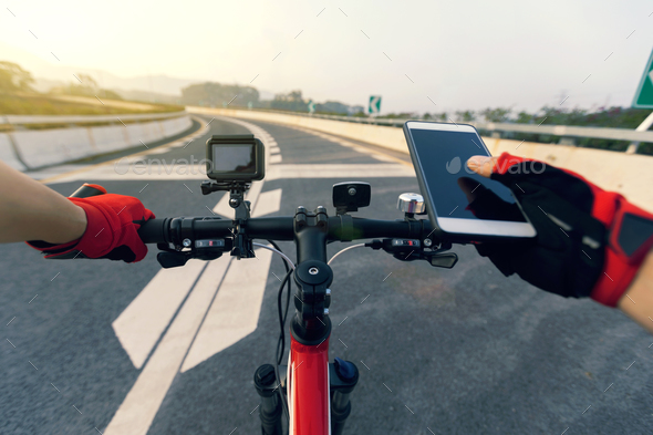 Use mobile phone while riding bike on highway - Stock Photo - Images