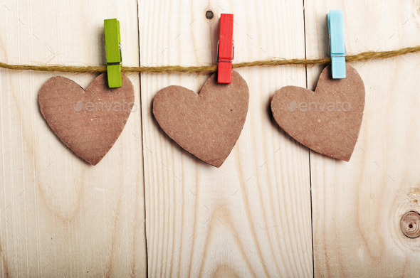 Handmade paper hearts hanging on clothesline over wood boards - Stock Photo - Images