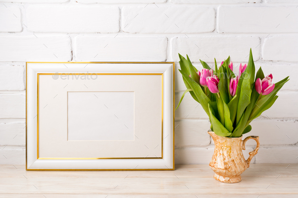 Gold decorated landscape frame mockup with bright pink tulips in - Stock Photo - Images