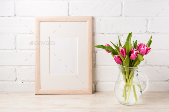 Wooden frame mockup with magenta pink tulips in glass pitcher ja - Stock Photo - Images