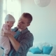 Dad Stands in a Room with a Small Baby in His Arms and Communicates with Him - VideoHive Item for Sale