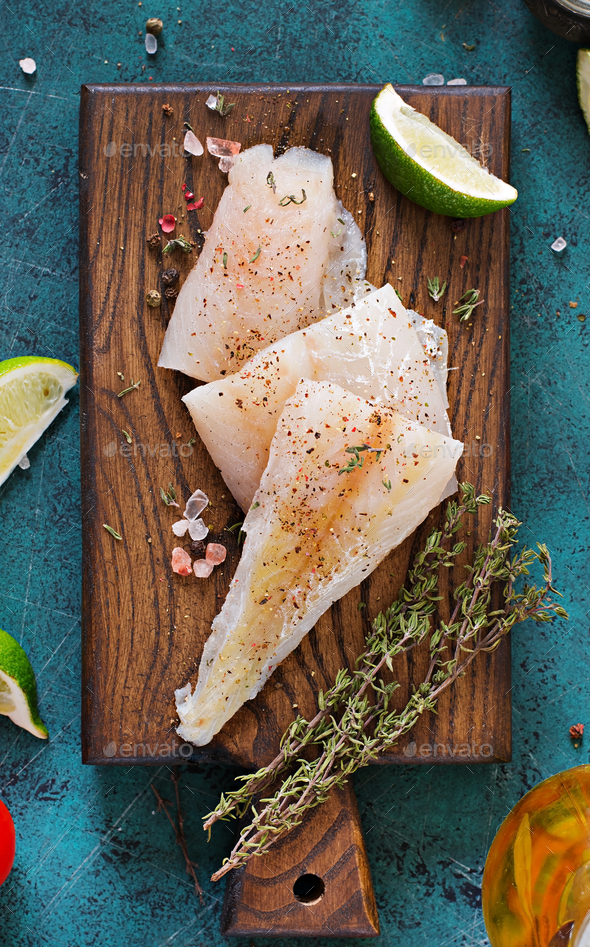 Fillet of white fish on a wooden board prepared for cooking. Flat lay. Top view - Stock Photo - Images