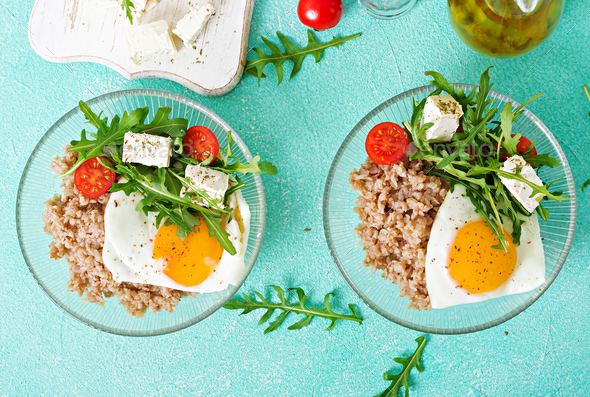 Healthy breakfast with egg, feta cheese, arugula, tomatoes  and buckwheat porridge  - Stock Photo - Images