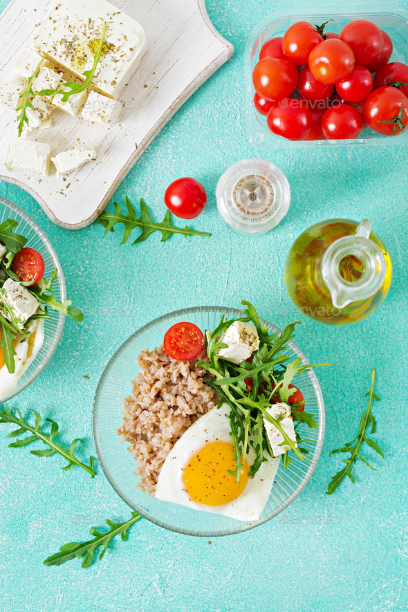 Healthy breakfast with egg, feta cheese, arugula, tomatoes  and buckwheat porridge - Stock Photo - Images