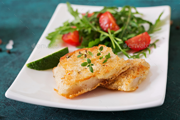 Fried white fish fillets and tomato salad with arugula. - Stock Photo - Images