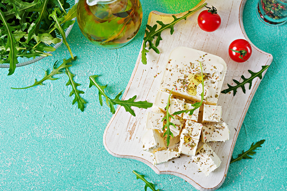 Feta cheese, cherry tomatoes and rucola on the table. Ingredients for salad. Top view - Stock Photo - Images