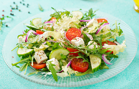 Salad of fresh vegetables - tomato, cucumber and feta cheese in Greek style - Stock Photo - Images