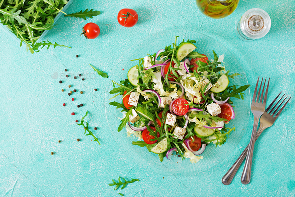 Salad of fresh vegetables - tomato, cucumber and feta cheese in Greek style. Flat lay. Top view - Stock Photo - Images