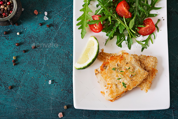 Fried white fish fillets and tomato salad with arugula. Top view - Stock Photo - Images