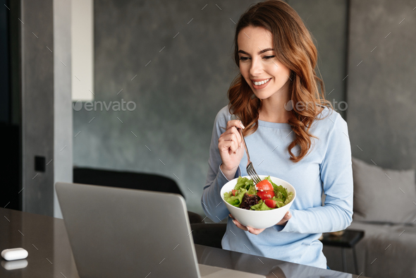Portrait of a pretty young woman eating fresh salad - Stock Photo - Images