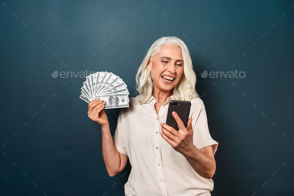 Mature happy old woman holding money using mobile phone. - Stock Photo - Images