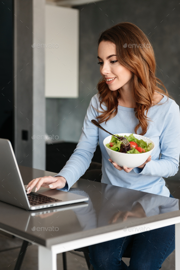 Portrait of a happy young woman eating fresh salad - Stock Photo - Images