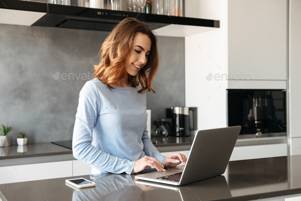 Portrait of a joyful young woman using laptop - Stock Photo - Images