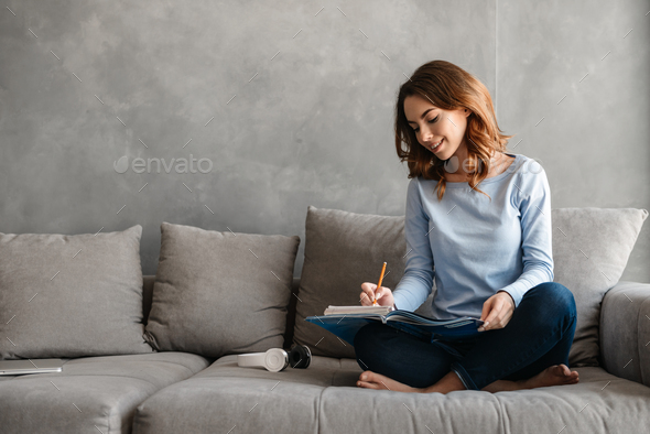 Portrait of a lovely young woman studying - Stock Photo - Images