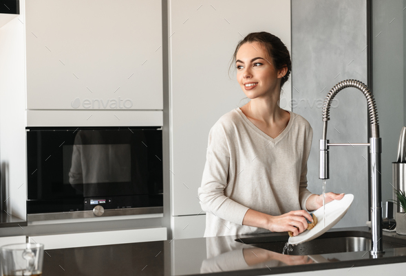 Portrait of a beautiful young woman washing dishes - Stock Photo - Images