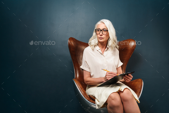 Serious mature old woman holding clipboard with documents writing notes. - Stock Photo - Images