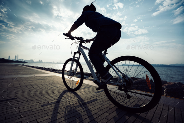 Silhouette of woman cycling on seaside during sunrise - Stock Photo - Images