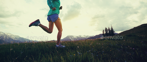 Running in grass and flowers on mountain top - Stock Photo - Images
