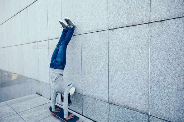 Hipster handstand on skateboarder - Stock Photo - Images