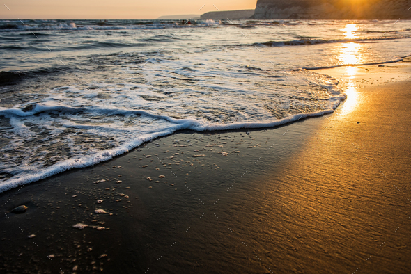 Waves approaching sandy beach during golden sunset - Stock Photo - Images