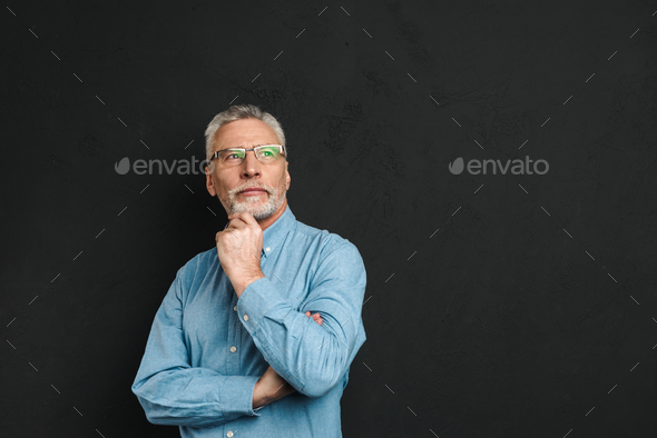 Portrait of elderly man 70s with grey hair and beard touching hi - Stock Photo - Images