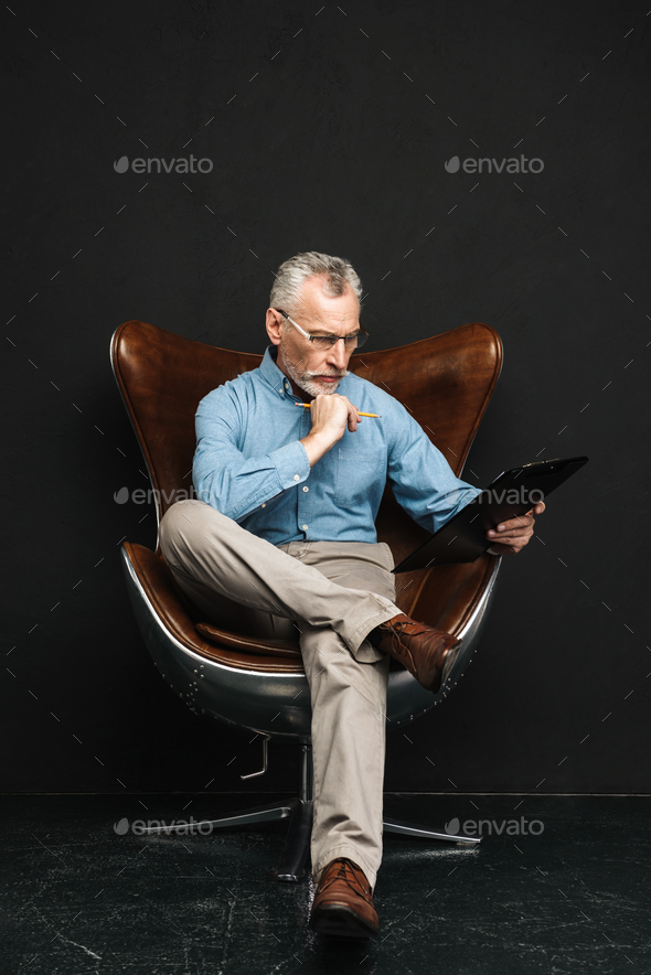 Full length photo of mature smart man working in office while si - Stock Photo - Images