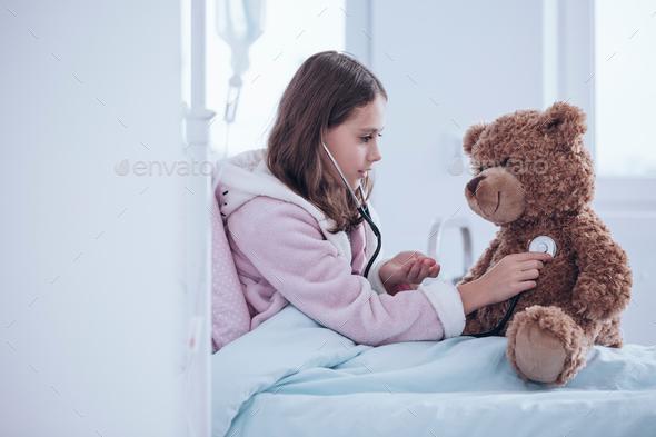 Girl examining teddy bear - Stock Photo - Images