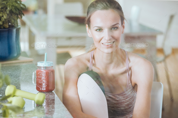 Smiling sportswoman drinking healthy cocktail - Stock Photo - Images