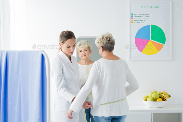 Dietician measuring patient's body circuit - Stock Photo - Images