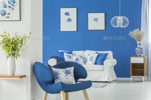 Blue armchair by white wall - Stock Photo - Images