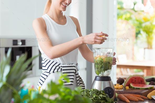 Happy vegan woman mixing vegetables - Stock Photo - Images