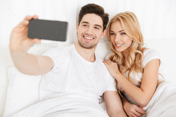 Cute young loving couple make selfie by by mobile phone - Stock Photo - Images