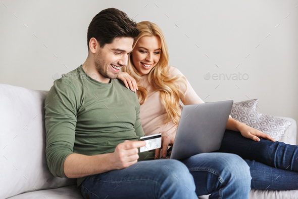 Happy young loving couple sitting on sofa holding debit card. - Stock Photo - Images