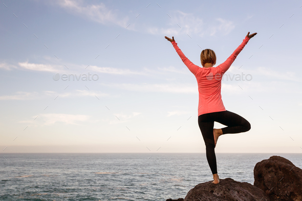 Woman meditating in yoga vrksasana tree pose - Stock Photo - Images