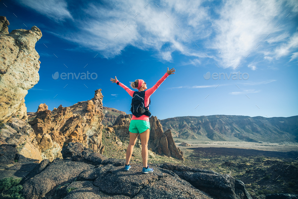 Woman hiker with arms outstretched enjoy mountains - Stock Photo - Images