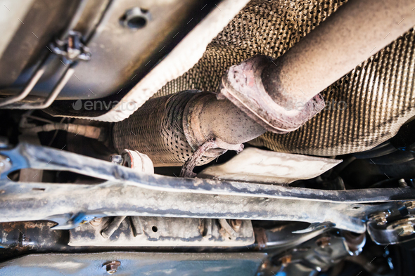 bottom view of broken corrugation muffler on car - Stock Photo - Images