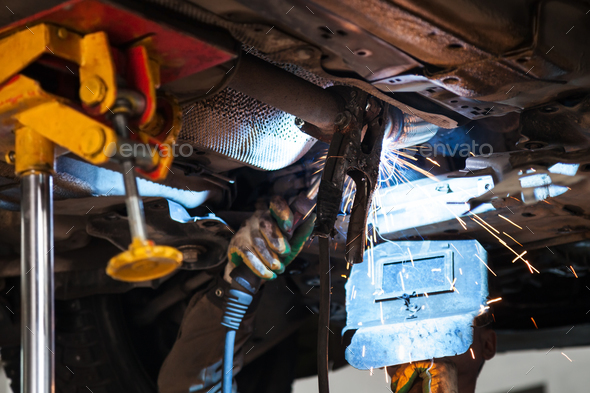 welder welds silencer on exhaust pipe - Stock Photo - Images