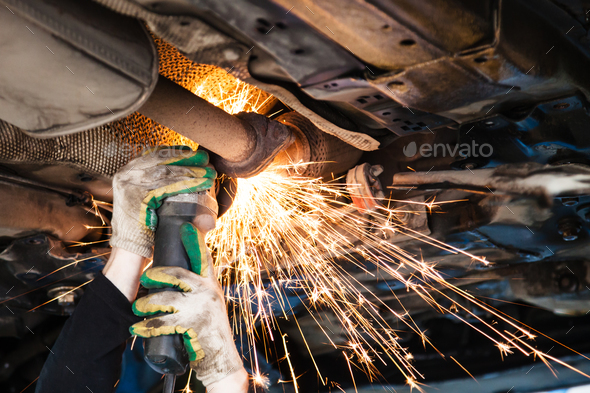 repairer cuts old silencer on car by angle grinder - Stock Photo - Images