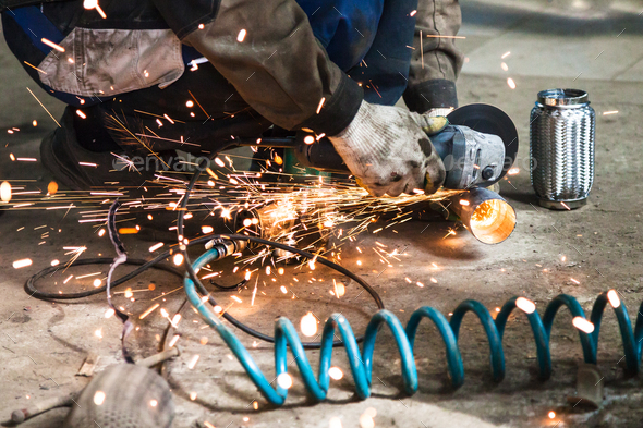 mechanic cuts new pipe for corrugation muffler - Stock Photo - Images