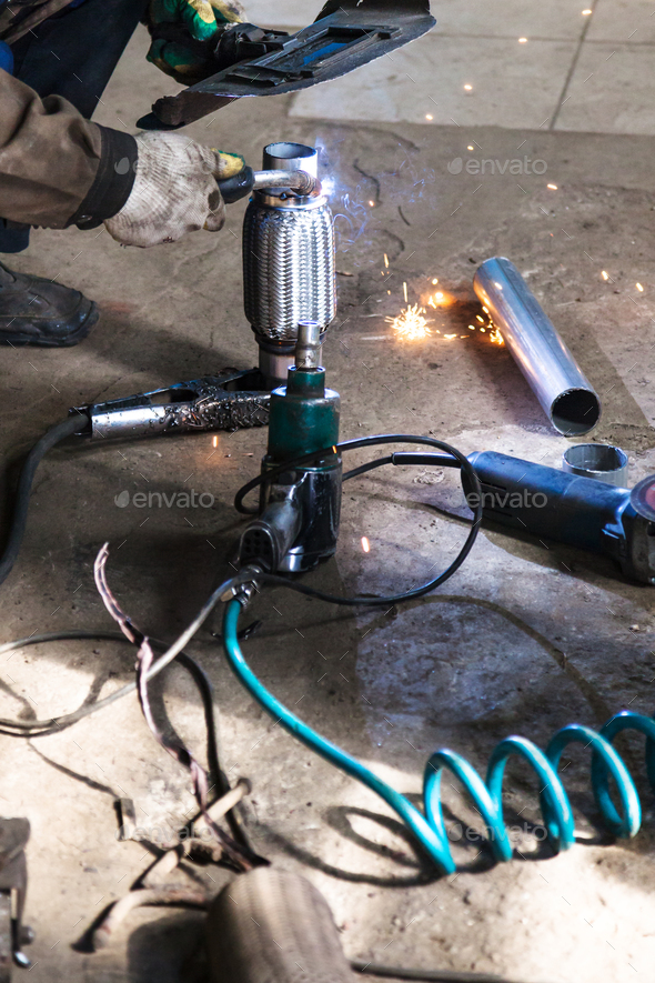 welder fixes pipe on corrugation muffler - Stock Photo - Images