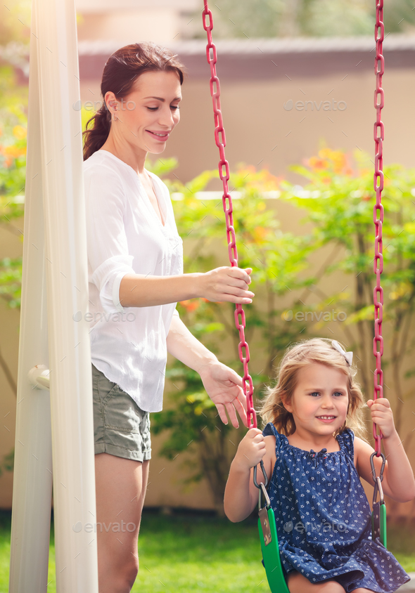 Mom rocks her daughter on a swing - Stock Photo - Images