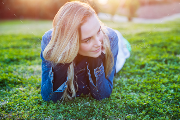 Pretty girl lying down on green grass - Stock Photo - Images