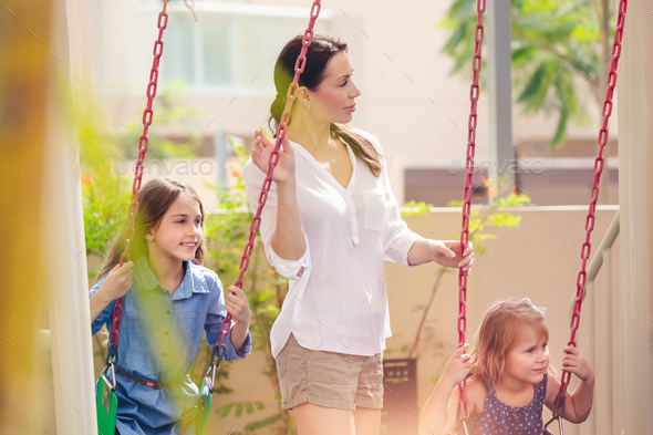 Mother with two daughters on playground - Stock Photo - Images