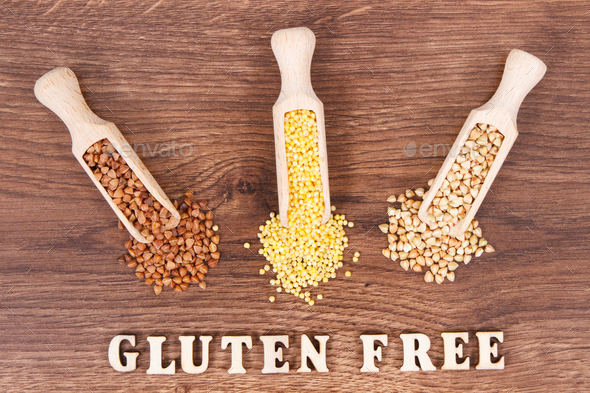 Gluten free inscription with various groats on rustic board, healthy food concept - Stock Photo - Images